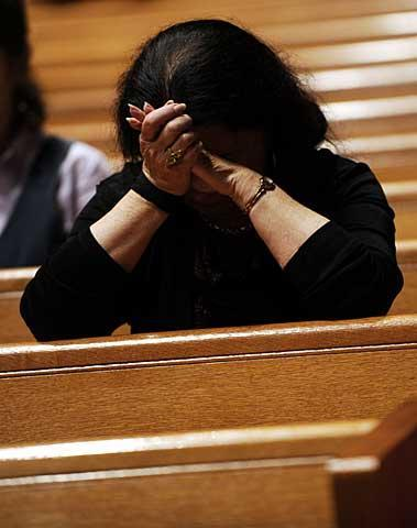 A woman prays after communion.
