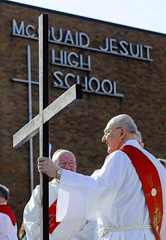 Deacon Bob Burke holds the cross.