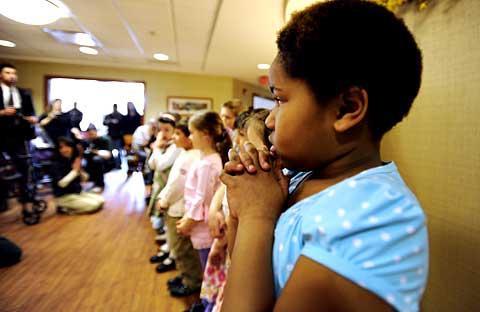 Alanna Davila prays with her classmates.