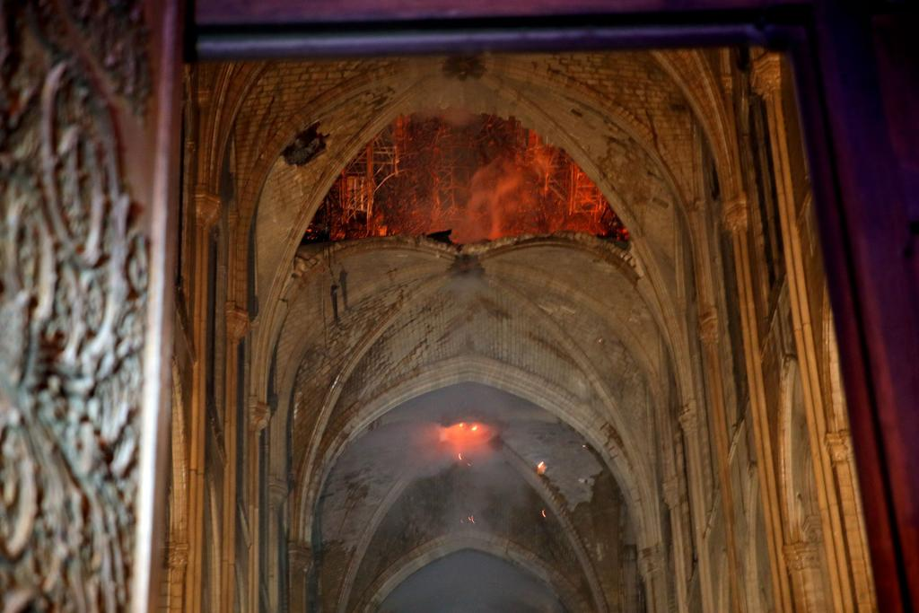 Flames and smoke are seen as the interior continues to burn inside the Notre Dame Cathedral in Paris April 16.(CNS photo by Philippe Wojazer, Reuters pool)