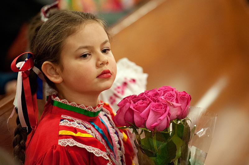 Eight-year-old Gabriela Perez holds roses to place near an image of Our Lady of Guadalupe.
