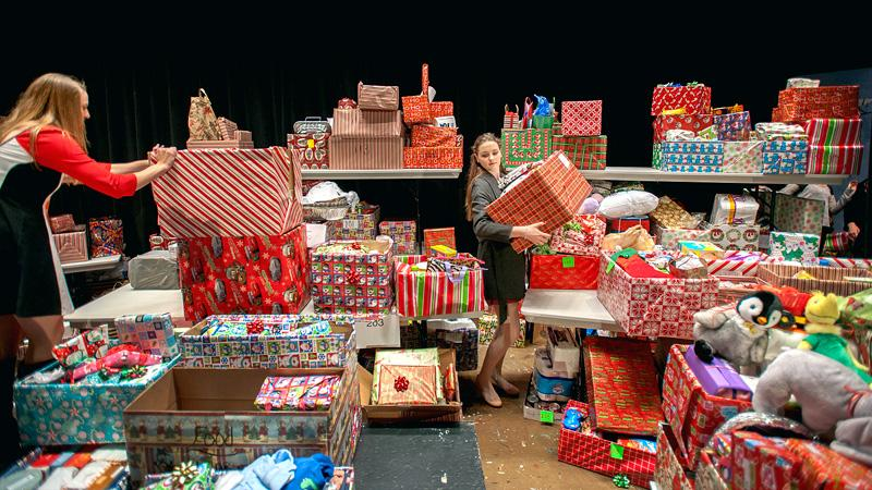 Students remove gifts from the stage in preparation for delivery.