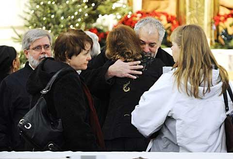 Parishioners embrace after the Mass.