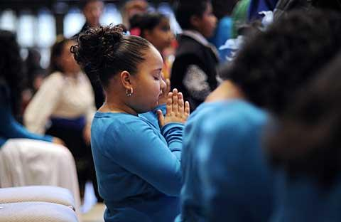 Eight-year-old Illiani Ramos prays during the Mass.