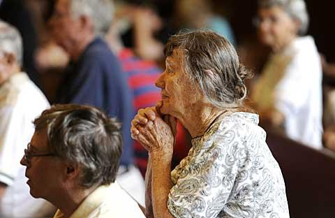 Longtime parishioner Hildegard Mitchell prays.