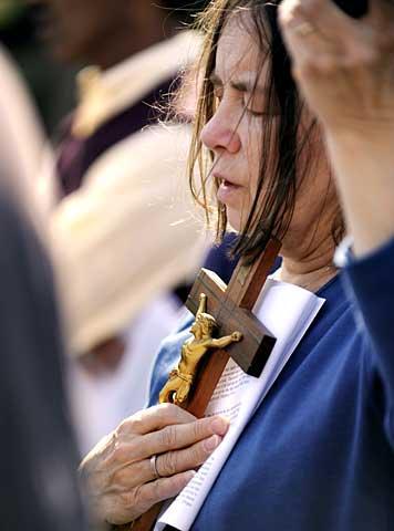 Christine Doyle prays during the procession.