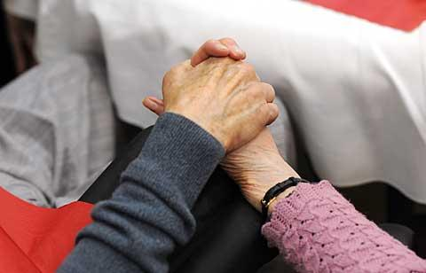 A couple holds hands during the Sweetheart Tea.