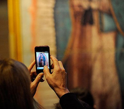 A parishioner takes a photo of the image.