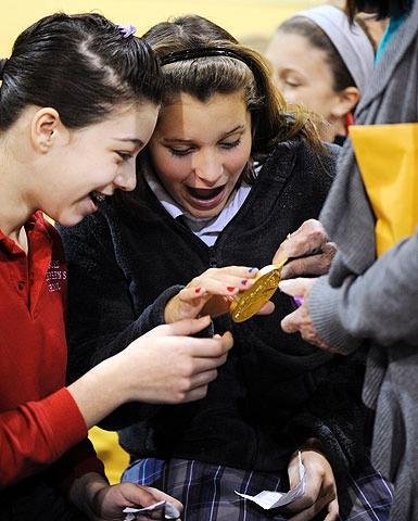 Tayah Payne (L) and Kaylee Smolinski look at the medal.