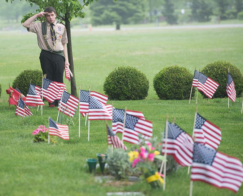 Boy Scout Troop 195 member Peter Burke salutes after placing a row of flags at a veteran's headstone in Rochester's Holy Sepulchre Cemetery on May 25.