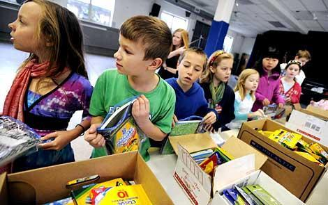 Students line up to organize school supplies.