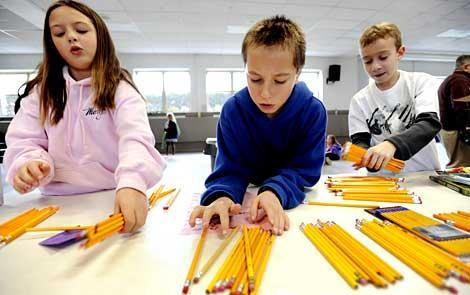 Sarah Hentschke, Ryan Kozarits and Oliver Smith organize pencils.