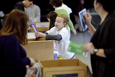 Oliver Smith helps fill boxes with donated school supplies.