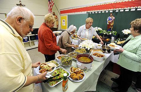 Parishioners make their way around the table.