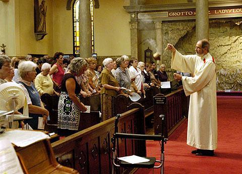 Deacon David Palma blesses parishioners.