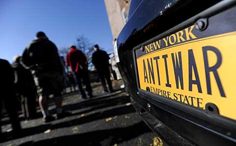 An anti-war license plate behind the veterans.