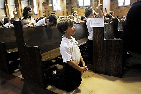 Michael Tierney kneels to pray during the Mass.