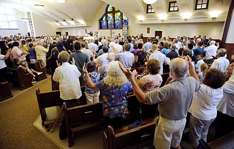 Parishioners join hands during the Lord's Prayer.