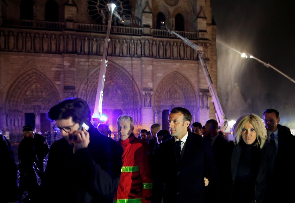 French President Emmanuel Macron, center right, and his wife, Brigitte, walk outside Notre Dame Cathedral after it suffered heavy damage from a fire April 15. (CNS photo by Philippe Wojazer pool via Reuters)