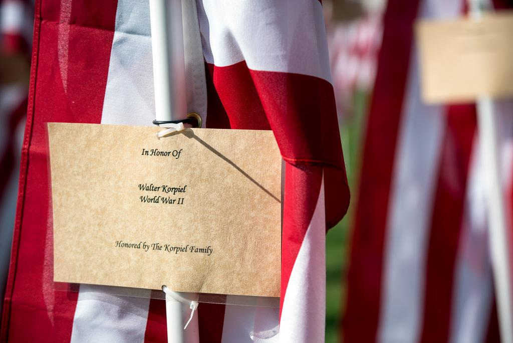 A card containing information about the person being honored is attached to each flag.