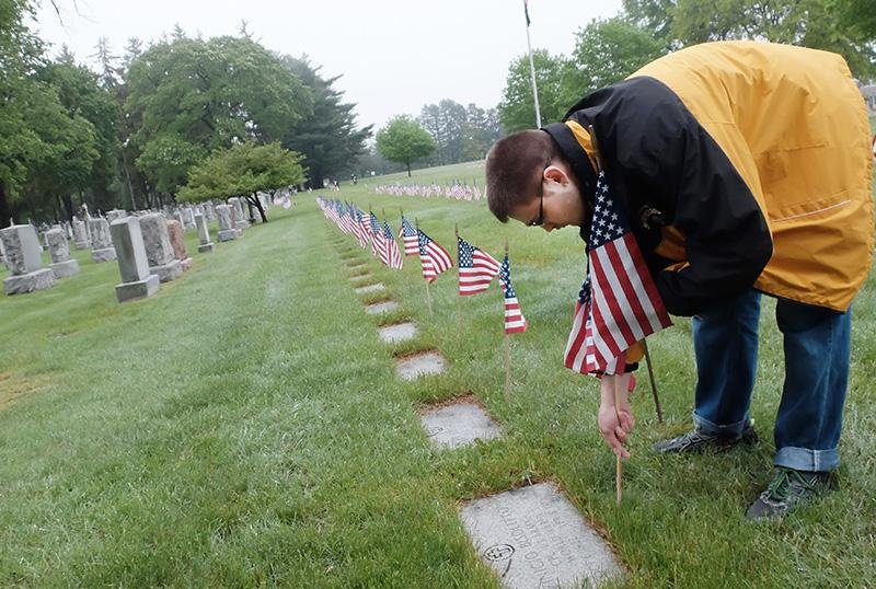 Boy Scout Troop 195 member Jason Patterson Jr. places a flag at a veteran's headstone.