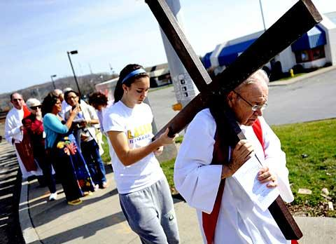 Father John Reif and Lauren Kelly carry the cross.