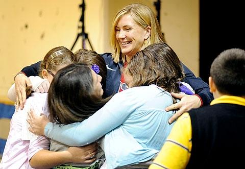 Musnicki grants a group hug to a group of students.