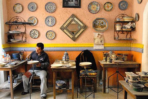 A man paints talavera ceramics in Puebla.