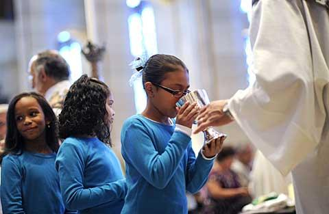 Nine-year-old Angelique Colón takes communion.