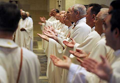 Priests extend their hands during the liturgy of the eucharist.
