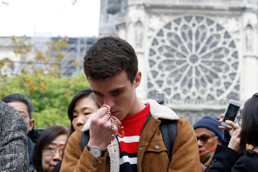 A young man holding a rosary prays in front of Notre Dame Cathedral April 16. (CNS photo by Paul Haring)