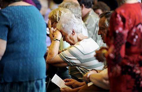Parishioners bow their heads in prayer.