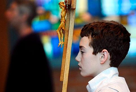 Brian Crowley carries the cross during Mass Feb. 4.