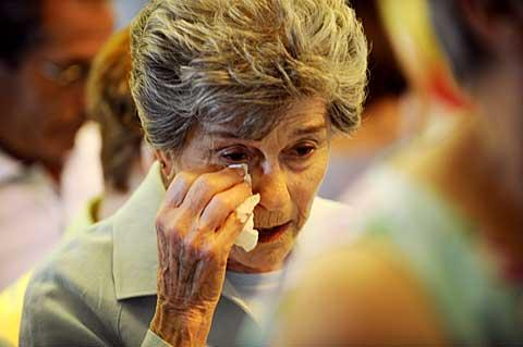 Gloria Mattiucci wipes away tears at the end of the Mass.