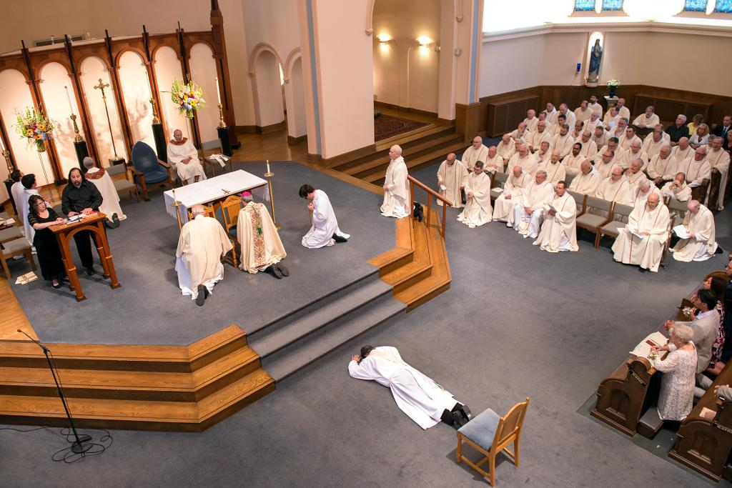 Father Kevin Mannara prostrates in front of the altar.