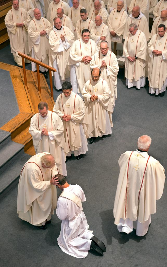 Priests line up to give their blessings to Father Kevin Mannara.