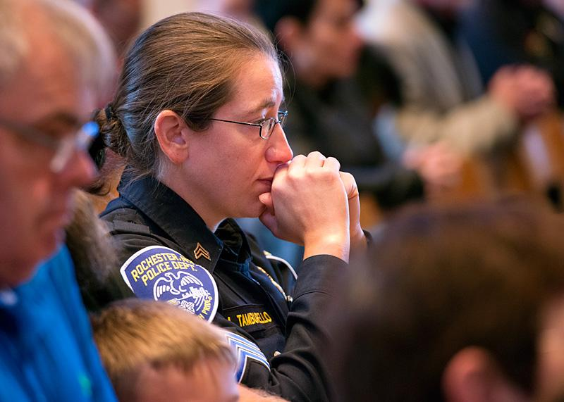 Sgt. Nicole Tamburello Conway of the Rochester Police Department kneels during the Liturgy of the Eucharist.