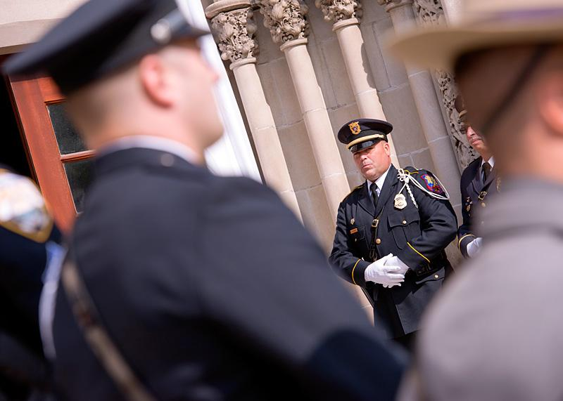 Officer Dave Robbins of the Greece Police Department stands at attention during the recessional.