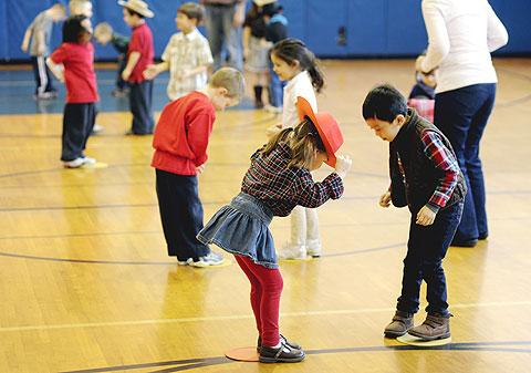 Kindergarteners bow to their partners while square dancing.