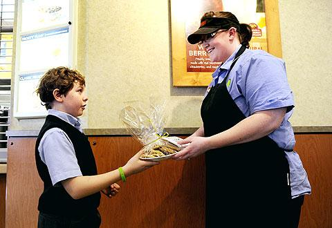 Carter Coston gives a cookie tray to Caitlyn Scott of Wendy's.