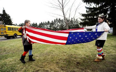 CTK students Michael Kiefer and Sophia Aureli fold the flag.
