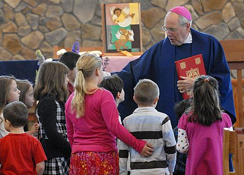 Bishop Emeritus Matthew H. Clark blesses the children during Mass.