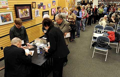 Fans wait in a long line to have their books signed.