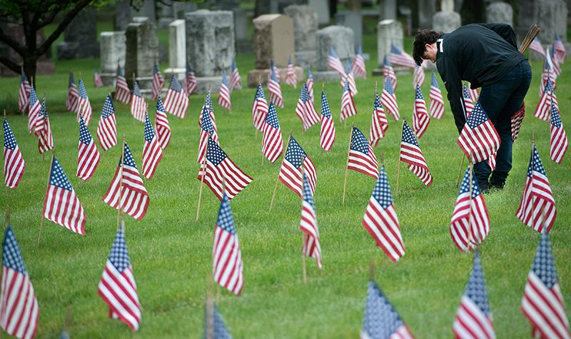Boy Scout Troop 195 members Ryan Papke places a flag at a veteran's headstone.