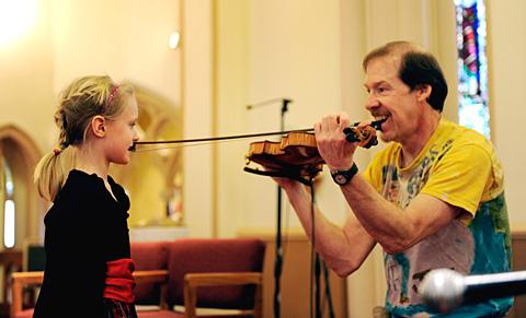 Isabelle Dennis helps Joe Dady play the fiddle.