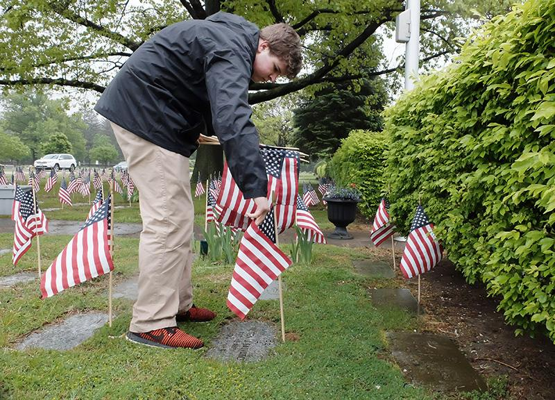Boy Scout Troop 195 member Deven Ebertz places a flag at a veteran's headstone.
