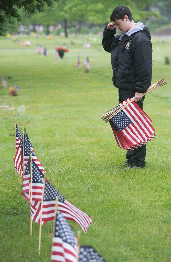Josh Washla, a member of Boy Scout Troop 195, salutes after placing a flag at a veteran's headstone in Rochester's Holy Sepulchre Cemetery May 25.