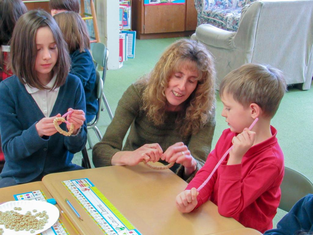 Teacher Audrey Walck works with students Elizabeth Chalker and Cavan Dennis on a service project making bird feeders for the Avon Nursing Home.