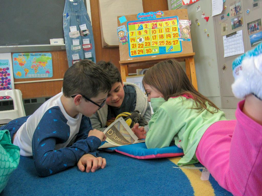 Sixth graders Michael Lenartowicz and Trevor Patel take turns reading to Kindergartener Madeline Flaherty on Pajama Day.