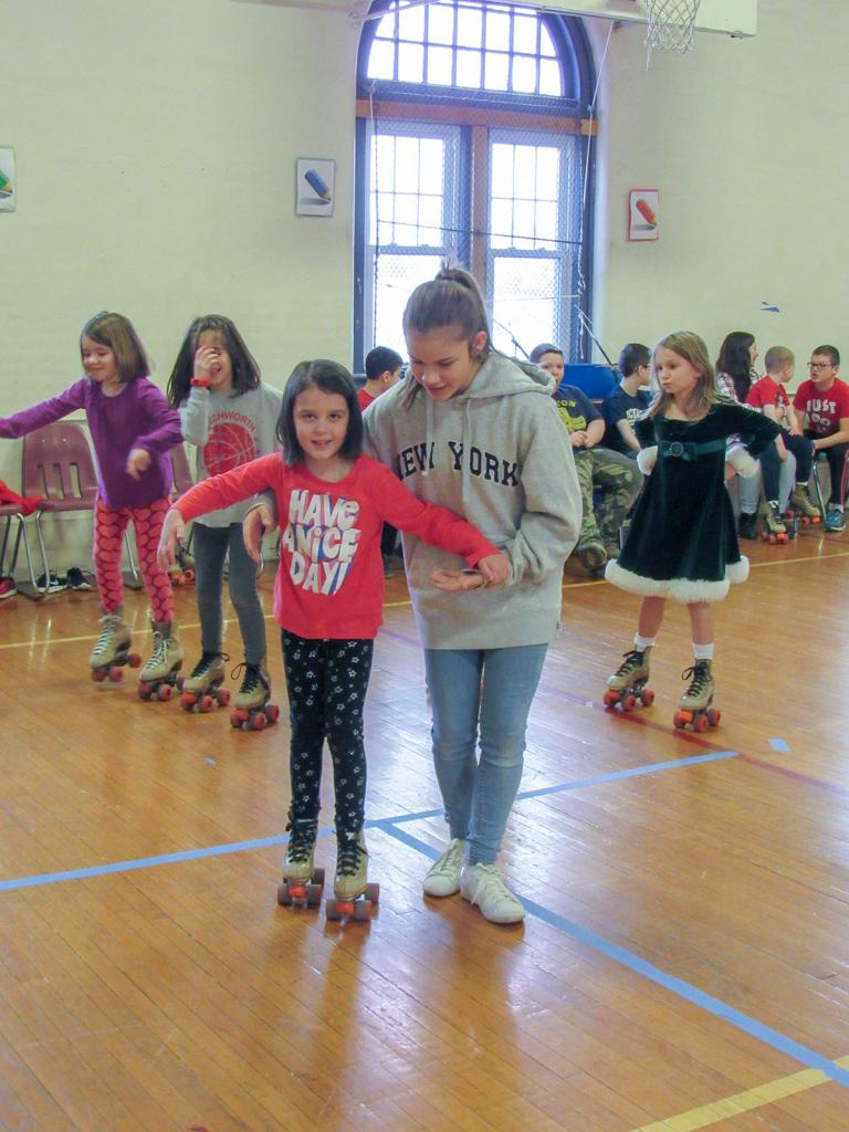 6th Grader Olivia Caiazzo helps teach Kindergartener Claire Bellanca how to Roller Skate.